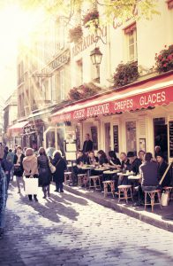 Paris, France - November 6, 2012: people enjoying their food at cafes of Montmartre - one of the famous area in Paris. View of the street in a sunny fall day.