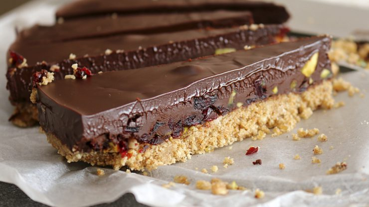 Rich chocolate ganache tart on a biscuit base with cranberries and pistachio nuts